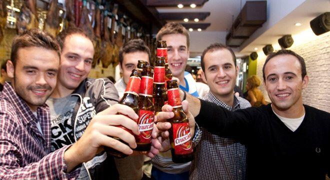 brindis entre muchachos con cervezas cruzcampo dentro del bar parlamento