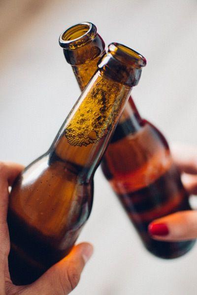 dos botellines de cerveza chocando para brindis