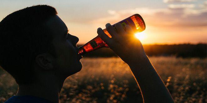 chico bebe cerveza frente campo y puesta de sol