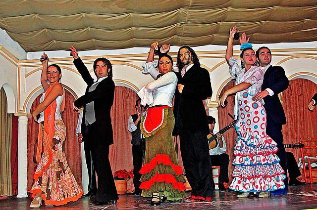 bailarines de sevillanas en parejas sobre un tablao flamenco